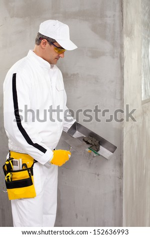 Worker mixing putty with a trowel - stock photo