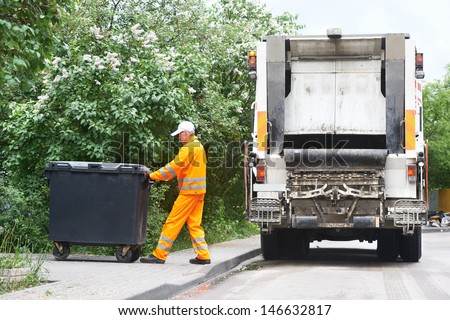 Worker of municipal recycling garbage collector truck loading waste and trash bin - stock photo