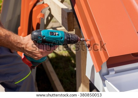 Worker on a roof with electric drill installing red metal tile on wooden house - stock photo