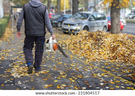 Worker on a street in autumn collects leaves with a leaf blower  - stock photo