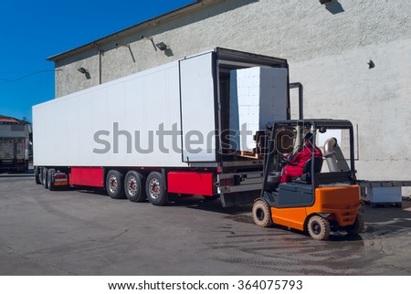 Worker on the loader unload white semi-trailer  - stock photo