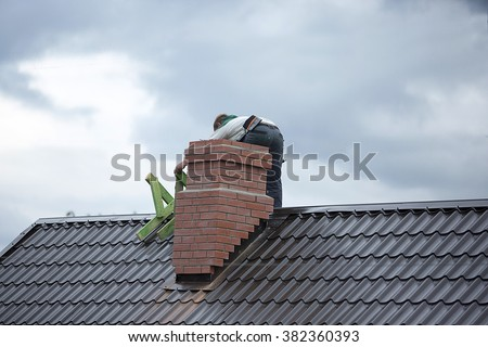 Worker on the roof repairs brick chimney - stock photo