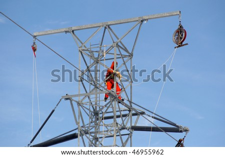 Worker on top of hydro tower - stock photo