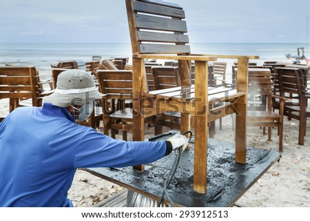 worker or carpenter, splash painted or repair, wooden chair - stock photo