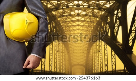 worker or engineer holding in hands yellow helmet for workers security on background of metal bridge over river in perspective buildings idea high way road junctions Empty Copy space for inscription - stock photo