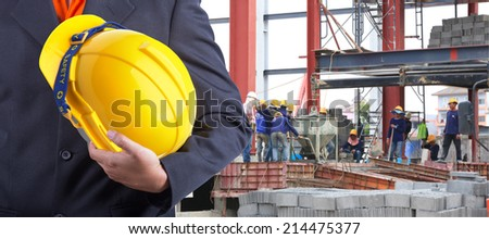 worker or engineer holding in hands yellow helmet for workers security on the background of a new building concrete floor with worker working hard  - stock photo