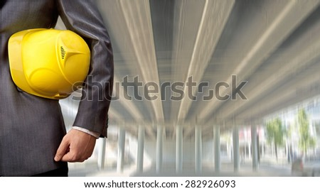 worker or engineer holding in hands yellow helmet for workers security on the background of a new concrete bridge over the river in perspective buildings gray idea of building new road junctions  - stock photo