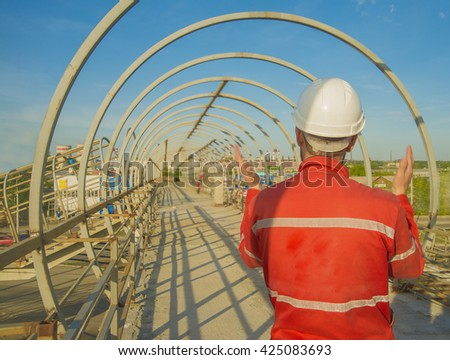 worker or engineer wear white helmet for workers security on the background of metal bridge over highway in perspective buildings. idea building road junctions. back view - stock photo