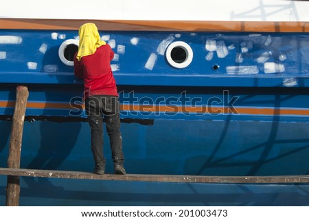 Worker paint and repair the ship at shipyard - stock photo