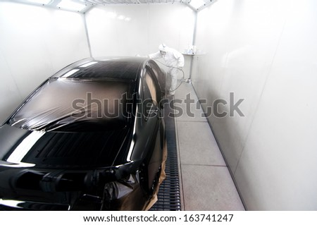 worker painting a black car in a special booth wearing protection gear - stock photo