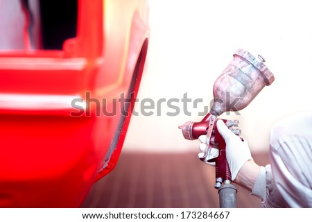worker painting a red car or element in a special garage, wearing a grey costume - stock photo