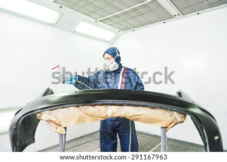 worker  painting auto car bumper in a paint chamber during repair work - stock photo