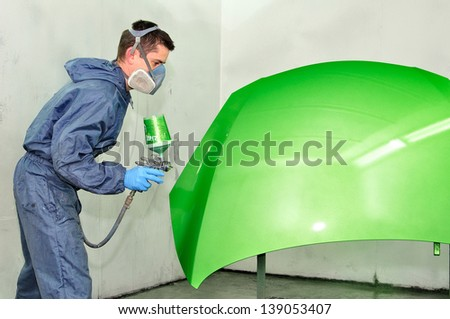 Worker painting green bonnet. - stock photo