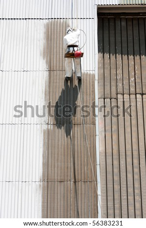 worker painting industrial warehouse - stock photo