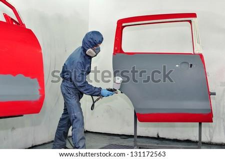 Worker painting red car door. - stock photo