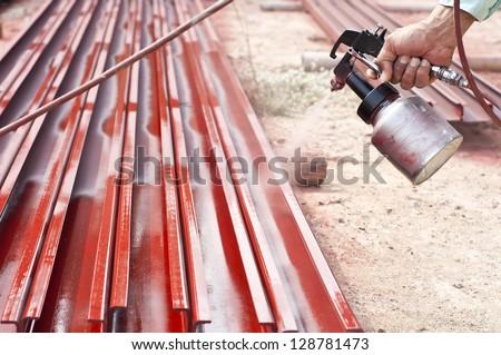 Worker painting steel bars using airbrush. - stock photo