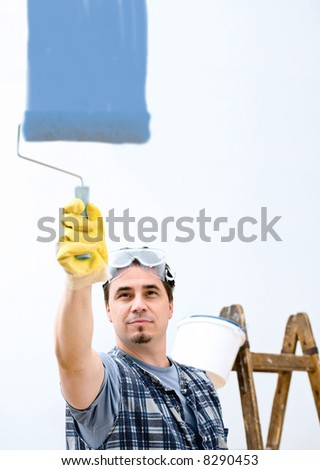 Worker painting the wall. - stock photo