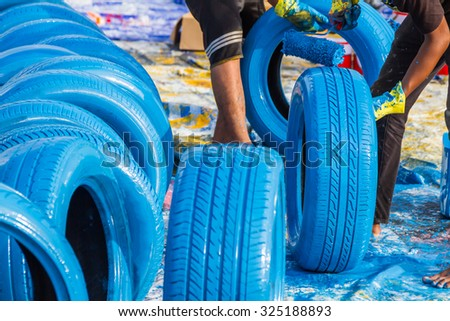 Worker painting  tire with roller at raceway on background. - stock photo