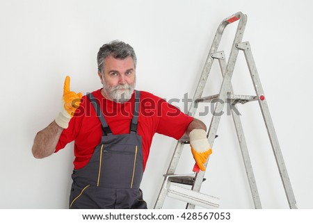 Worker painting wall to white and gesturing, with ladder and paint roller - stock photo