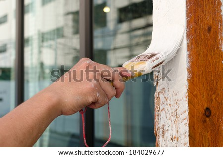 Worker painting wood with paint brush. - stock photo