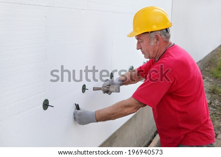Worker placing expansion anchor to styrofoam sheet insulation of the wall with hammer - stock photo