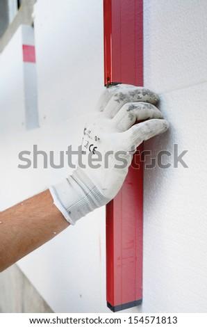 Worker placing styrofoam sheet insulation using level tool - stock photo