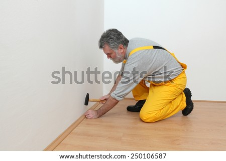 Worker pound in a nail to batten for laminate floor, hammer nail,  floating wood tile - stock photo