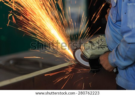 Worker preparation steel plate by hand grinding machine - stock photo