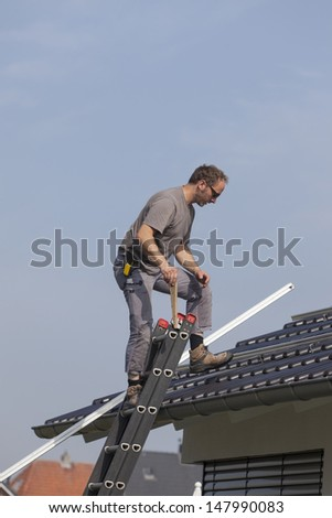 worker preparing the roof to install alternative energy photovoltaic solar panels. - stock photo