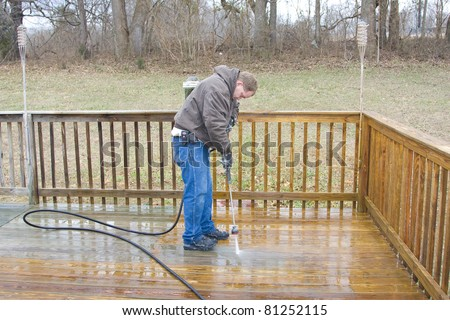 Worker pressure washing deck on rear of house - stock photo