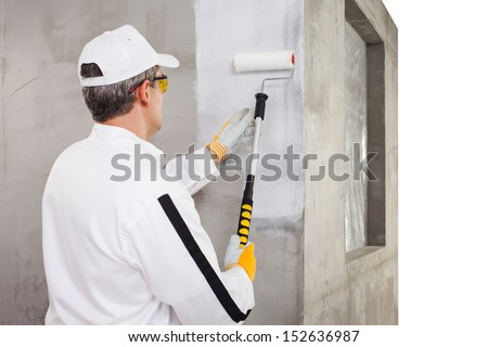Worker priming with a paint roller - stock photo