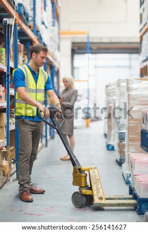 Worker pulling trolley with boxes in warehouse - stock photo