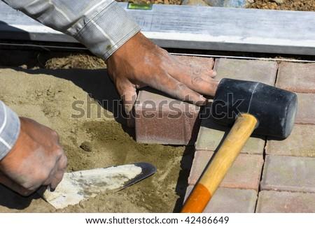 worker puts sidewalk tile - stock photo