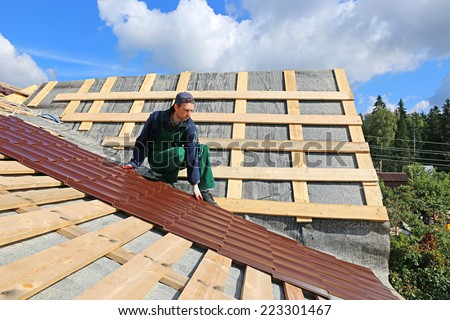 Worker puts the metal tiles on the roof of a wooden house - stock photo