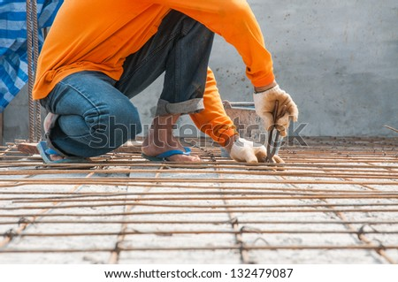 Worker, rebar gridwork across a floor for strength - stock photo