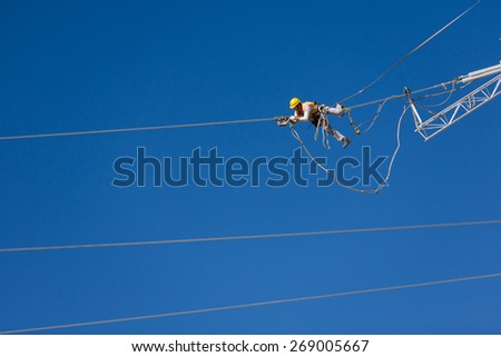 Worker repairing a high voltage industrial power energy line. Great for energy, safety and technology themes. : Almada, Portugal - October 02, 2008  - stock photo