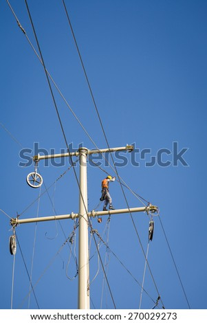 Worker repairing a high voltage industrial power energy line. No face is visible. Great for energy, safety and technology themes. - stock photo