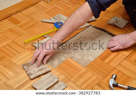 Worker repairing wooden floor damaged due to moisture or water, with hands and tools - stock photo