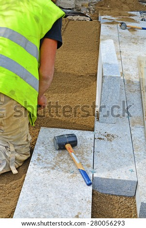 Worker screeding sand bedding to level for laying granite paver blocks. Permeable paving installation series. - stock photo