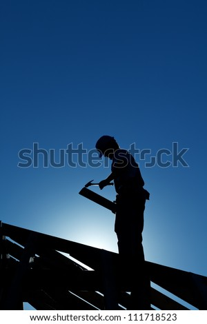 Worker silhouette on the roof structure in back light against deep blue sky - stock photo