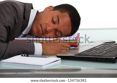 Worker sleeping on his desk - stock photo