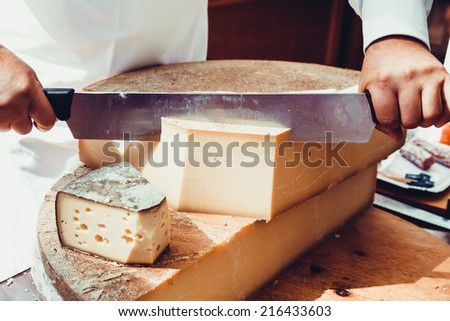 Worker slicing the cheese. Close up of Cutting cheese. - stock photo