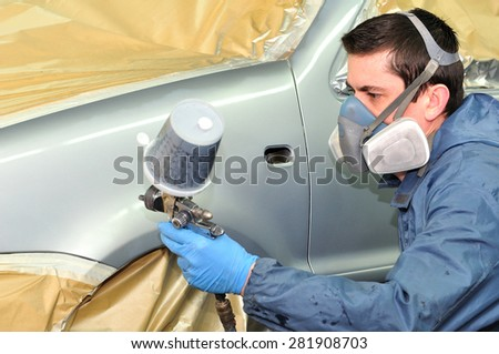 Worker spraying gray base coat. - stock photo