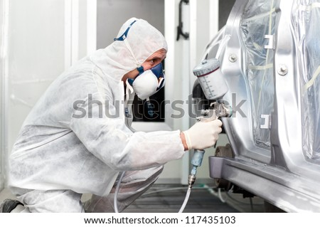 worker spraying grey paint on a car in special painting booth - stock photo