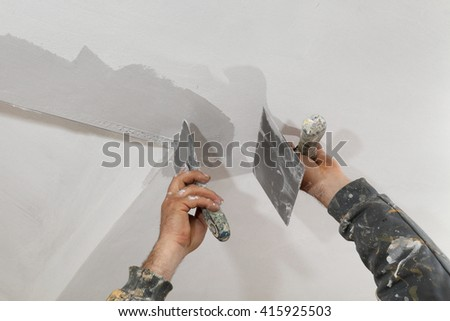 Worker spreading  plaster to wall, corner protecting batten install, repairing works - stock photo