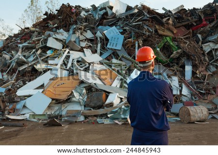 worker standing in front of pile of disposed objects in recycling center - stock photo