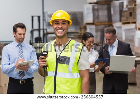 Worker standing with scanner in front of his colleagues in a large warehouse - stock photo