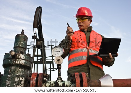 worker tells the radio station and holding laptop,best focus vest workers, head, glasses, helmets, laptops, pump oil soft focus - stock photo
