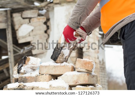 Worker throws bricks near the burned old house - stock photo
