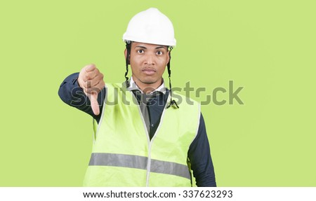 Worker thumb down on green background - stock photo